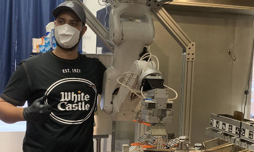 A White Castle team member standing next to the Flippy robot.